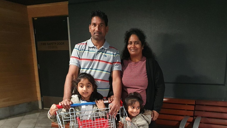 The Murugappan family stands outside a supermarket with a trolley