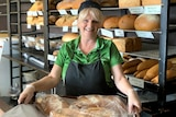 Ms Mayoss smiles and holds a pan of loaves of breads, in front of a rack of loaves.