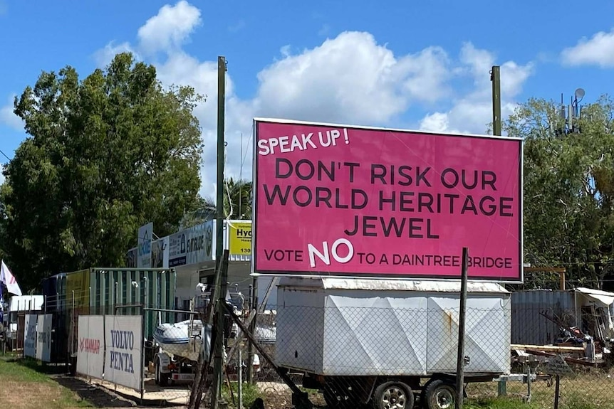 """A large pink sign on top of a trailer which reads """"Speak up, don't risk our world heritage jewel, vote no to a Daintree bridge"""""""