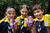 Three children holding up drink cans.