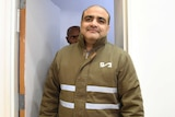 Mohammed Al Halabi, director of the Gaza branch of World Vision, wearing a green jacket in a court room.