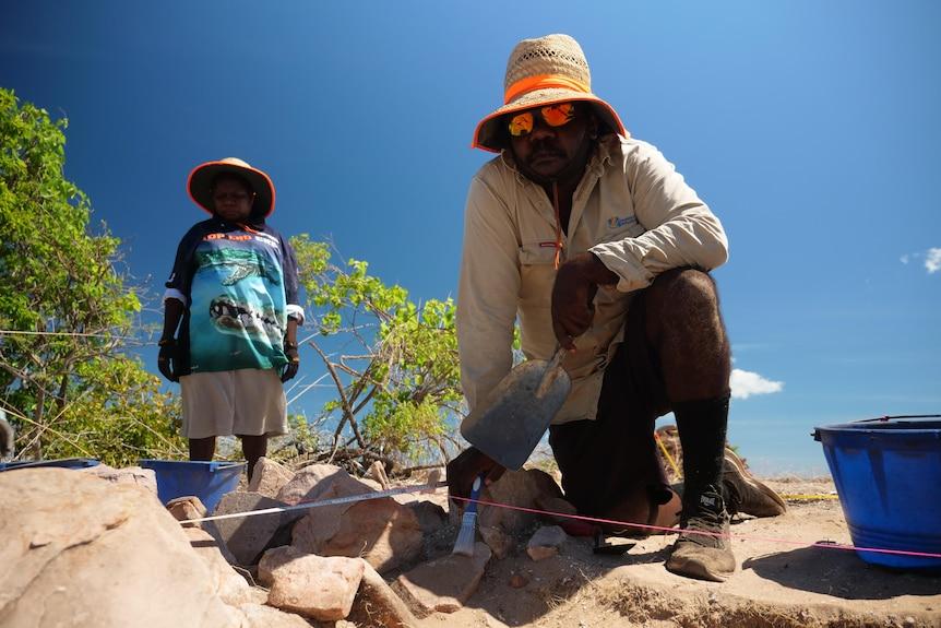 An Aboriginal man kneels at an archaeological dig.