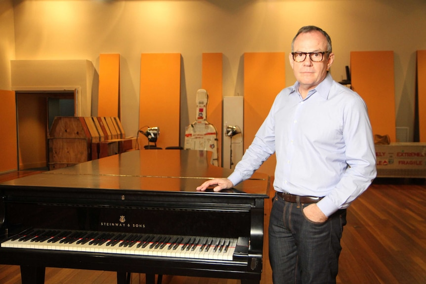 A man in glasses and a business shirt next to a piano