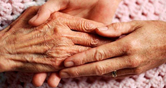 Elderly woman's hands  being held by another pair of hands.