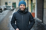 A young man wearing a beanie smiles in an Italian street.