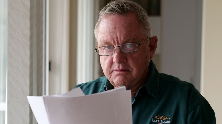 A seated Kevin Barracough wearing glasses looks out from behind a financial document