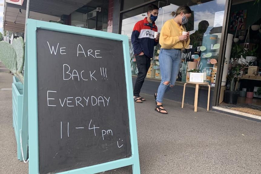 A chalkboard bears a welcome message outside a business.