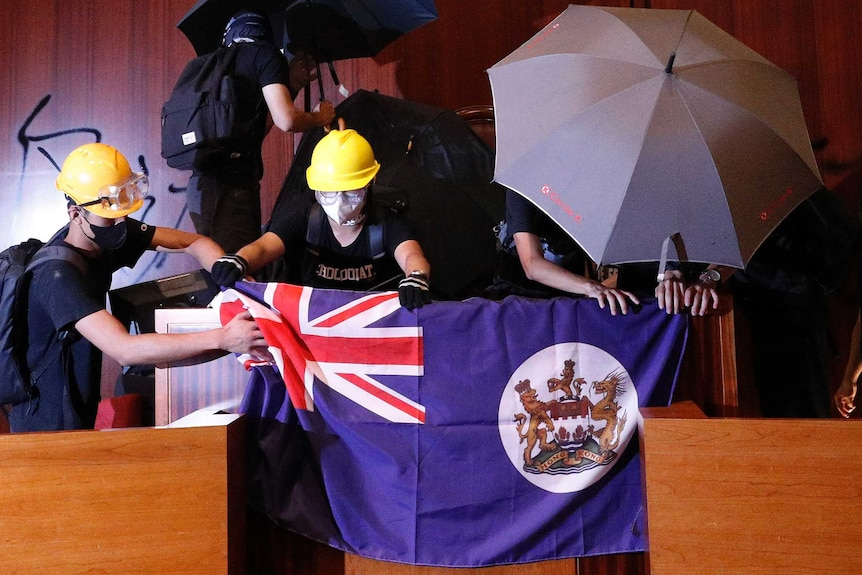 Protesters put a Hong Kong colonial flag and deface the Hong Kong logo at the Legislative Chamber.