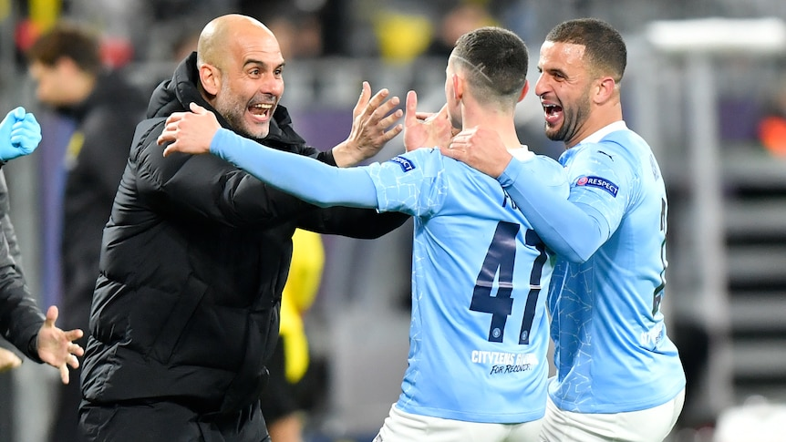 Pep Guardiola smiles and reaches for Phil Foden's face in celebration. Kyle Walker has his arm around Foden