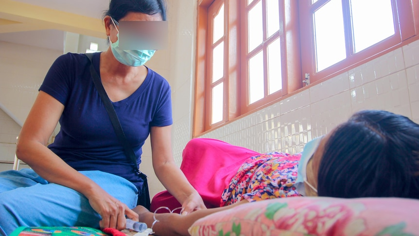 A woman in a face mask and blue t-shirt treats a woman lying on a bed
