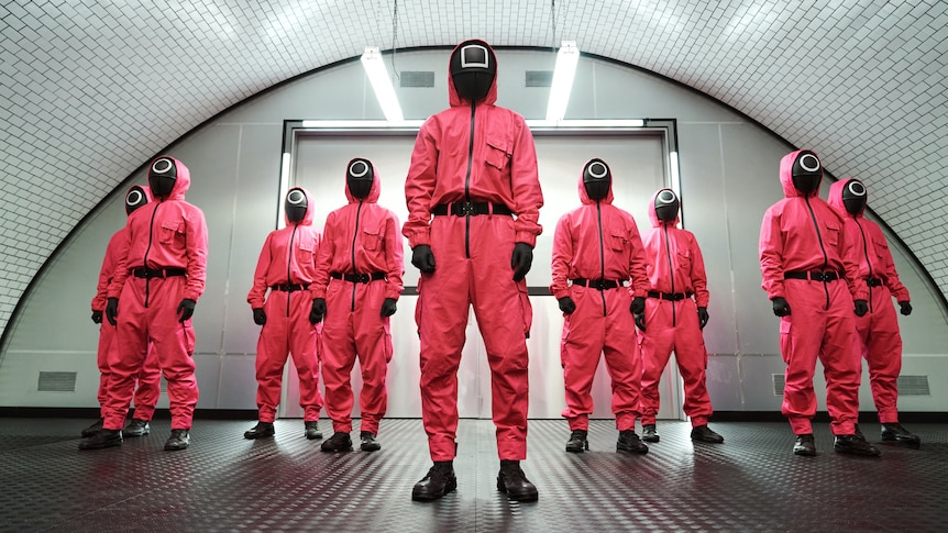 A still from the Netflix show Squid Game, with a group of people in pink hazmat suits and black masks