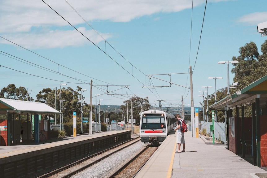 A train pulls into Seaforth Station in Gosnells with a passenger standing on the platform waiting.