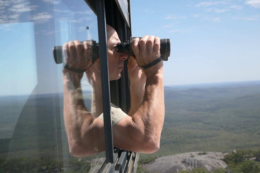 A man holding a pair of binoculars looks out over the landscape from a tower.