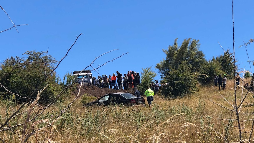 A group of people gather at the site of a car crash, while police attend.