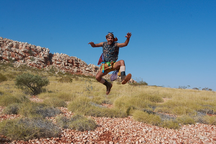 A man in aviation cap and goggles, tool belt, shorts and sleeveless shirt leaps in the air in rocky spinifex desert landscape.