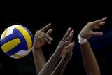 Yanelis Santos Allegne and Nancy Carrillo de la Paz jump to block a spike