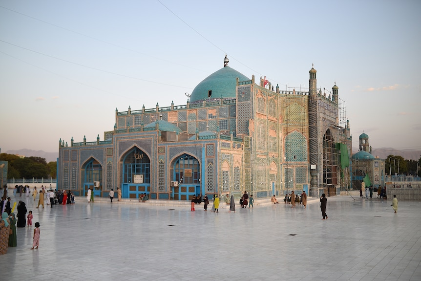 A beautiful golden mosque with blue domes can be seen at the centre of a paved square.