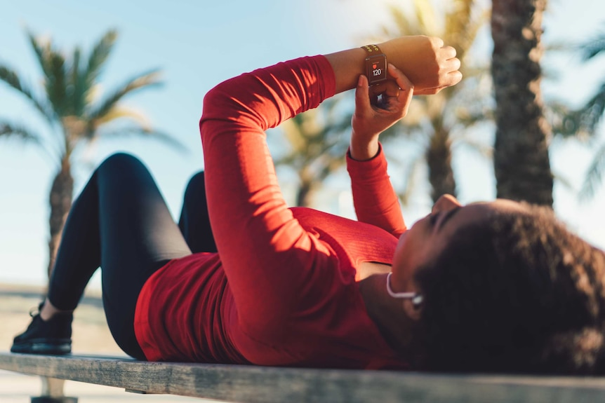 A woman resting on a park bench and tracing her pulse on a smartwatch.