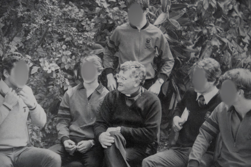 A black and white photo of Daniel McMahon surrounded by students whose faces have been blurred.