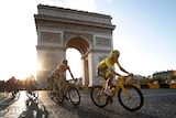 The sun sets behind the Arc de Triomphe with riders in front of it.