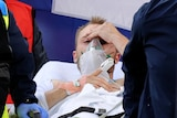 Christian Eriksen lies on a stretcher holding his head, with an oxygen mask on