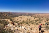 A arid Central Australian landscape with a few hikers on the track.