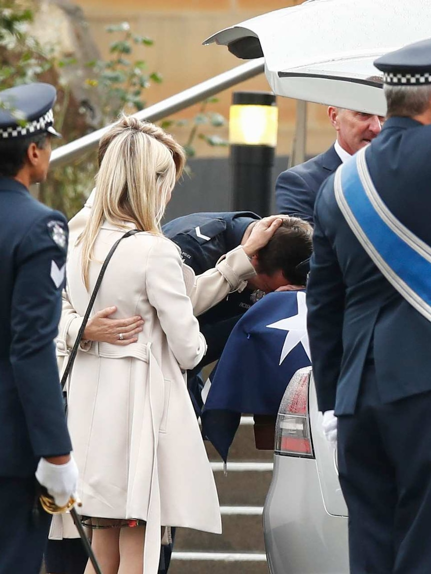 Constable Alex Prestney lays his head on his brother's coffin and his mother, Belinda, lays a h and on his head.