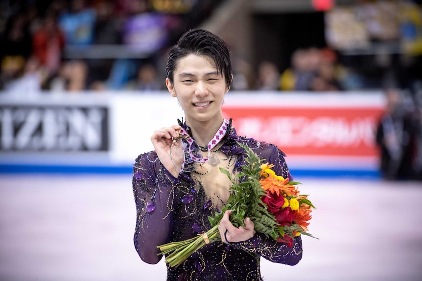 Yazuru Hanyu holds a medal and flowers and smiles towards the camera.