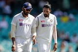 Two Indian players in cricket whites talk while walking on the field.