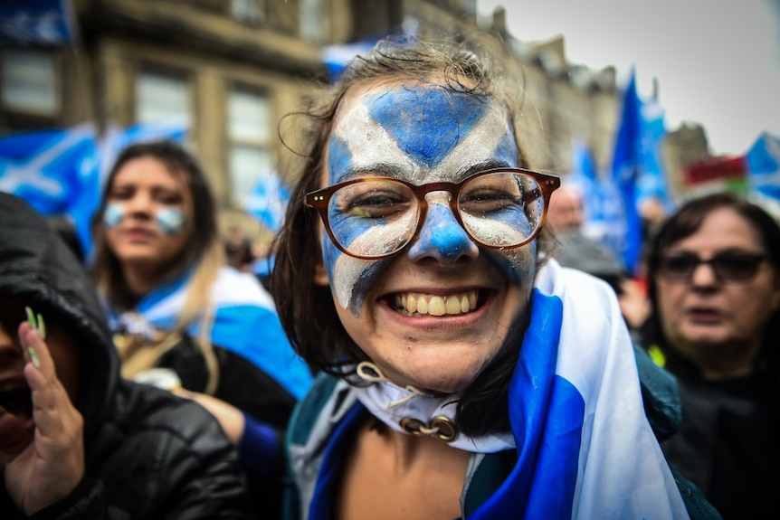 A woman wearing glasses. with a blue and white cross painted on her face, smiles at the camera
