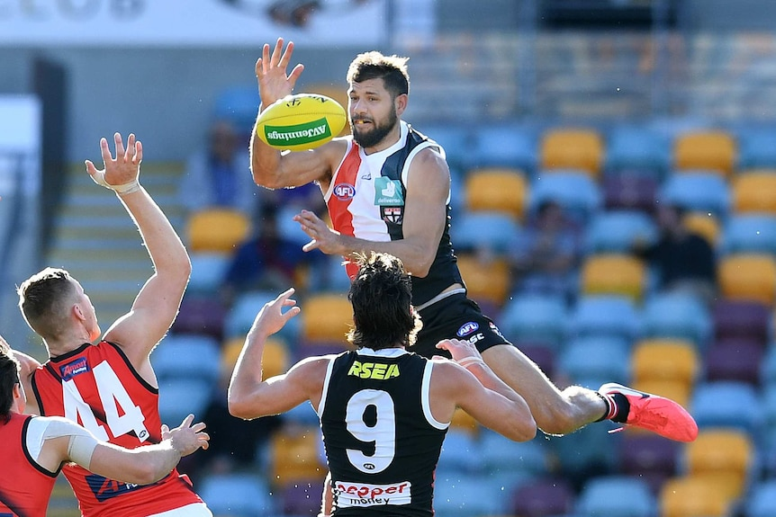 Paddy Ryder leaps towards a yellow ball and looks to catch it with one hand above the ball
