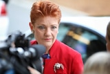 Pauline Hanson, wearing a red jacket with a silver brooch, looks past a camera in the foreground.