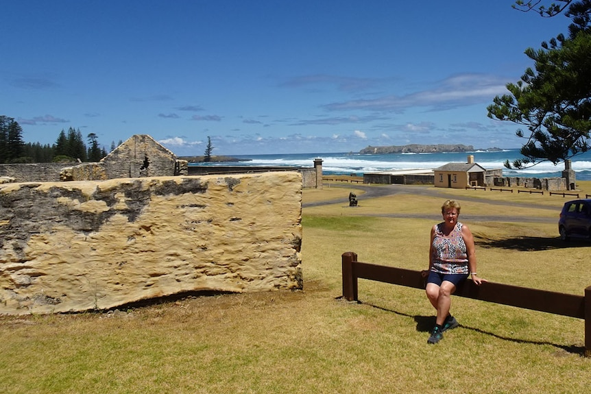 Luella Wait sits on a log near historic building ruins on Norfolk Island.