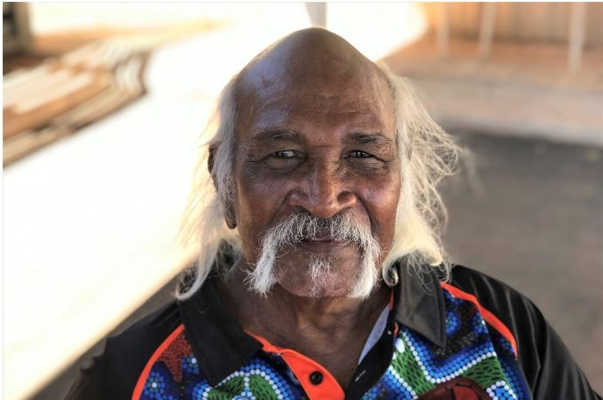 Close up shot of face of indigenous man with straggling white hair looking into the camera