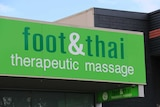 A green sign on a building reading Foot and Thai Therapeutic Massage.