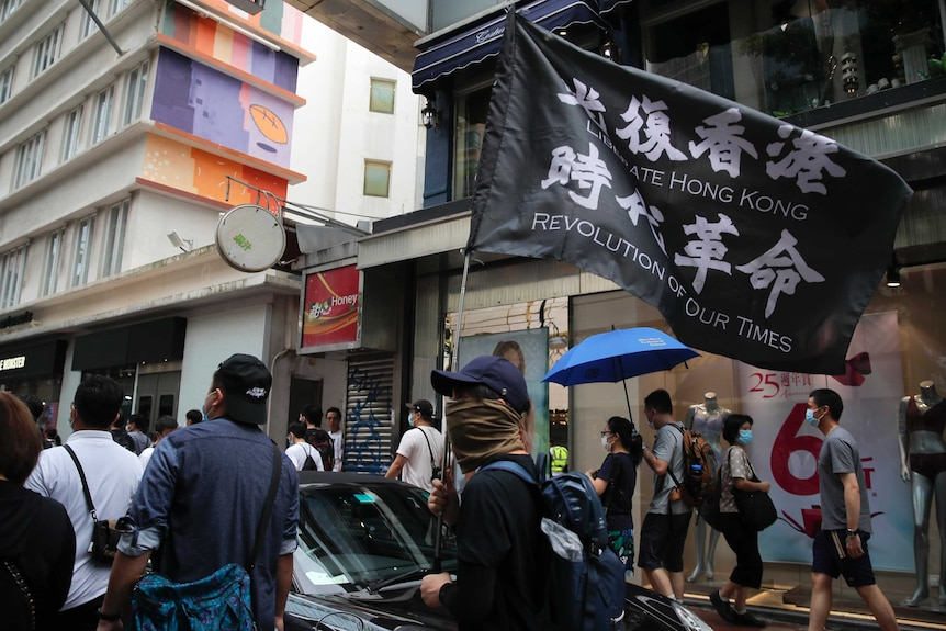 """Protesters carry the flag which reads """"Liberate Hong Kong, revolution of our time"""" in Causeway Bay."""