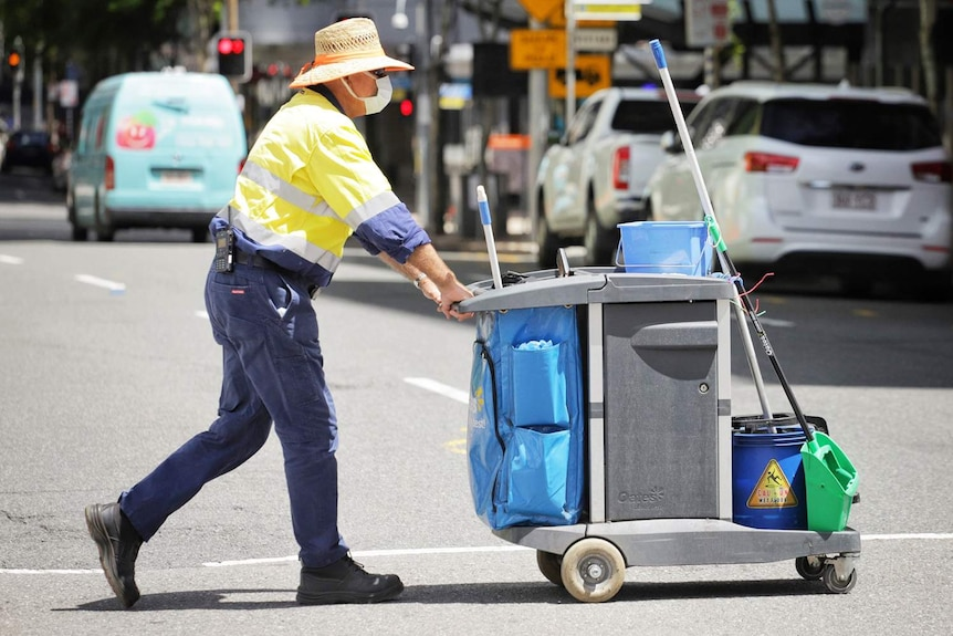 Council cleaning worker wearing a mask pushing a trolley crosses George Street in Brisbane city on January 11, 2021.