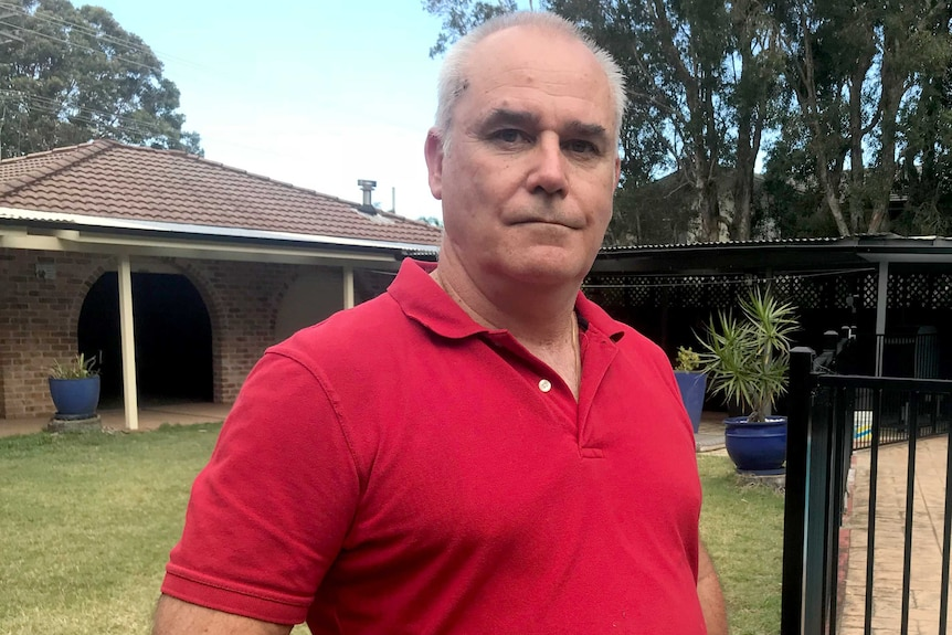 Peter stands in a backyard next to a pool fence with a single-storey brick and tile home visible behind him.