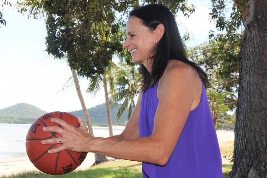 A woman throws a basketball at the beach