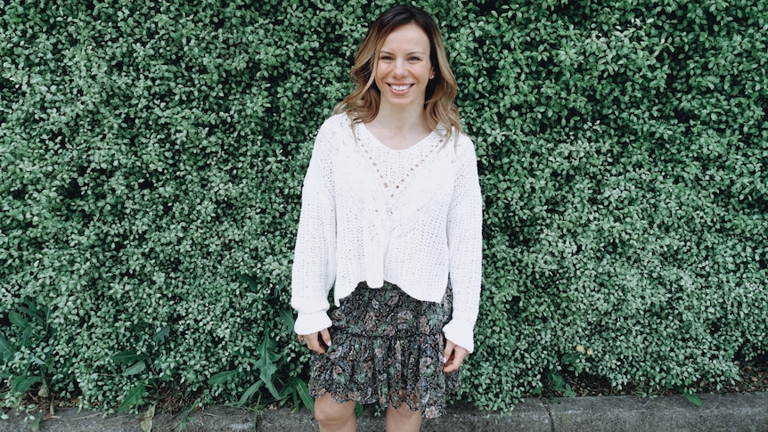 Lena Moxon smiles while standing in front of a wall of green plants.