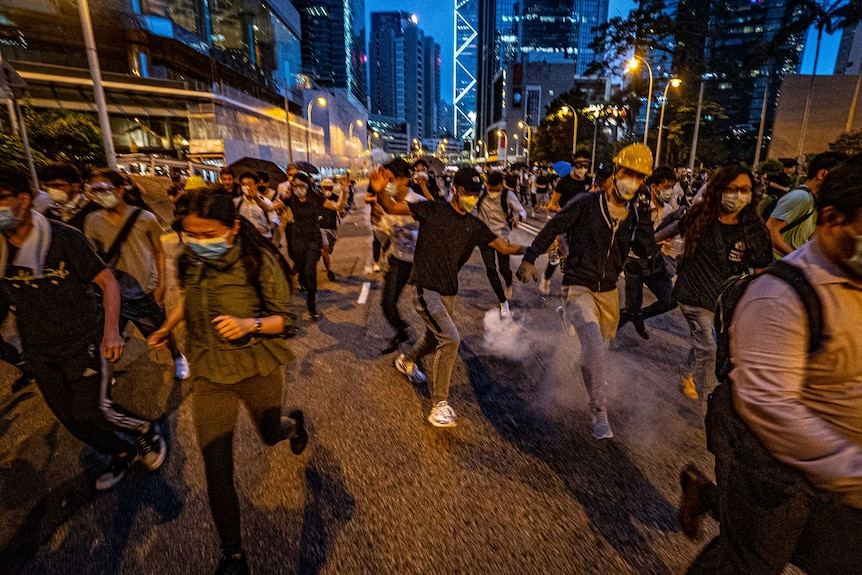 People are blurry as they run on a street, some smoke from tear gas can be seen rising, they wear hard hats, surgical face masks