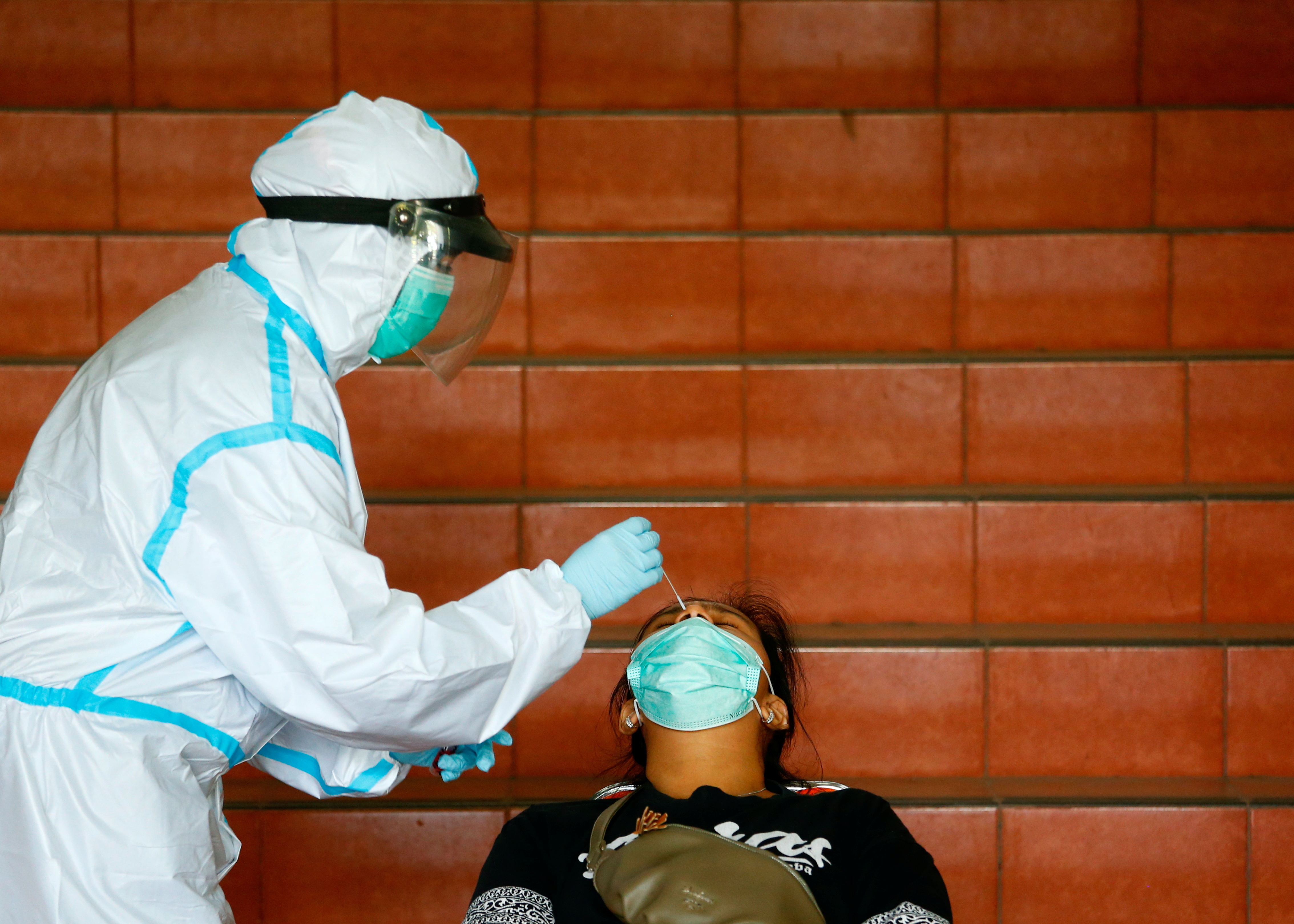 A medical worker in PPE takes a nasal swab sample from a woman