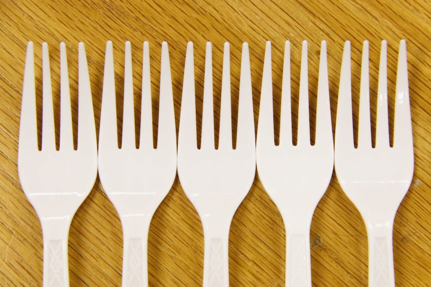 Five plastic forks in a row.