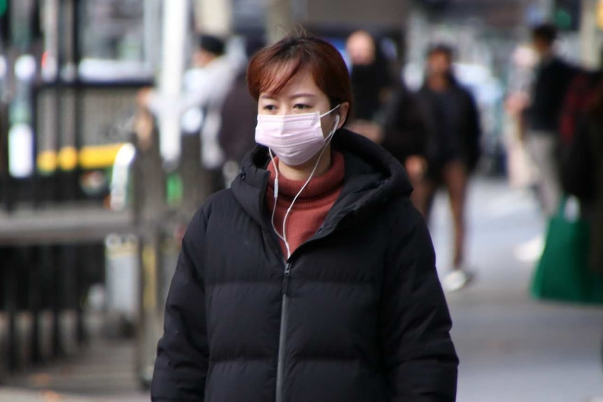 A woman is pictured wearing a face mask on a Melbourne street.