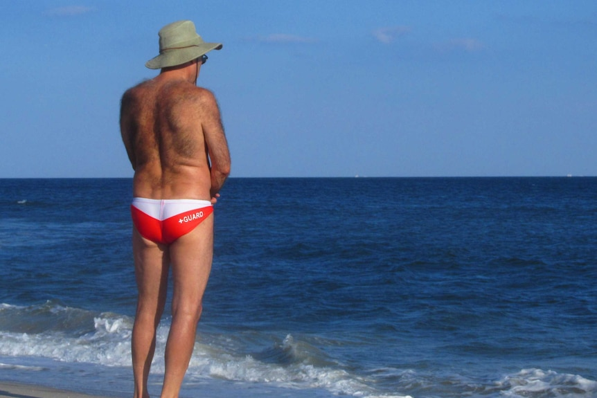 A man with a hairy back stands in the sun at the beach