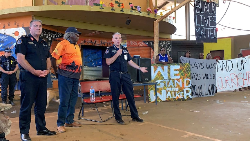 Travis Wurst stands in front of banners as he addresses the Yuendumu community.