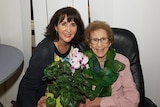 An elderly mother and her daughter smiling, holding a bouquet of flowers.