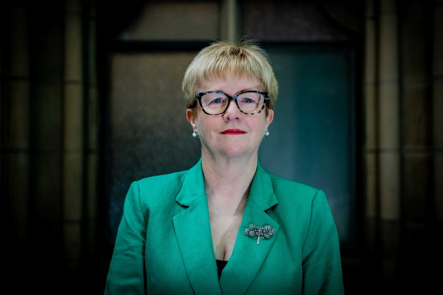 Helen Seares wears a green jacket and looks at the camera.