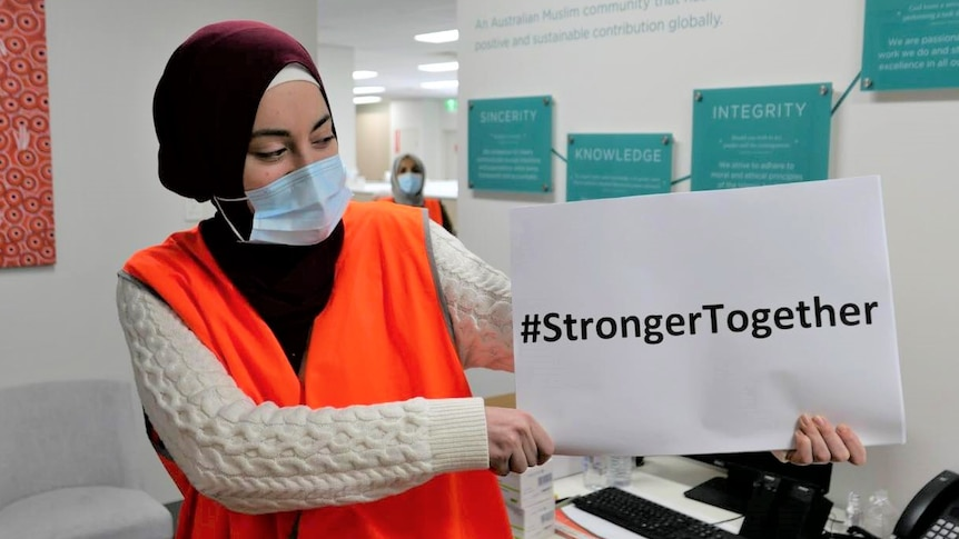 """A woman in a hijab and hi-vis vest holds a sign reading """"Stronger Together""""."""