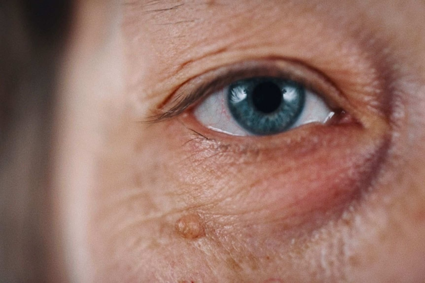 A still from Hoda Afshar's video work Agonistes, a close up shot of a white wrinkled skin and a blue eye